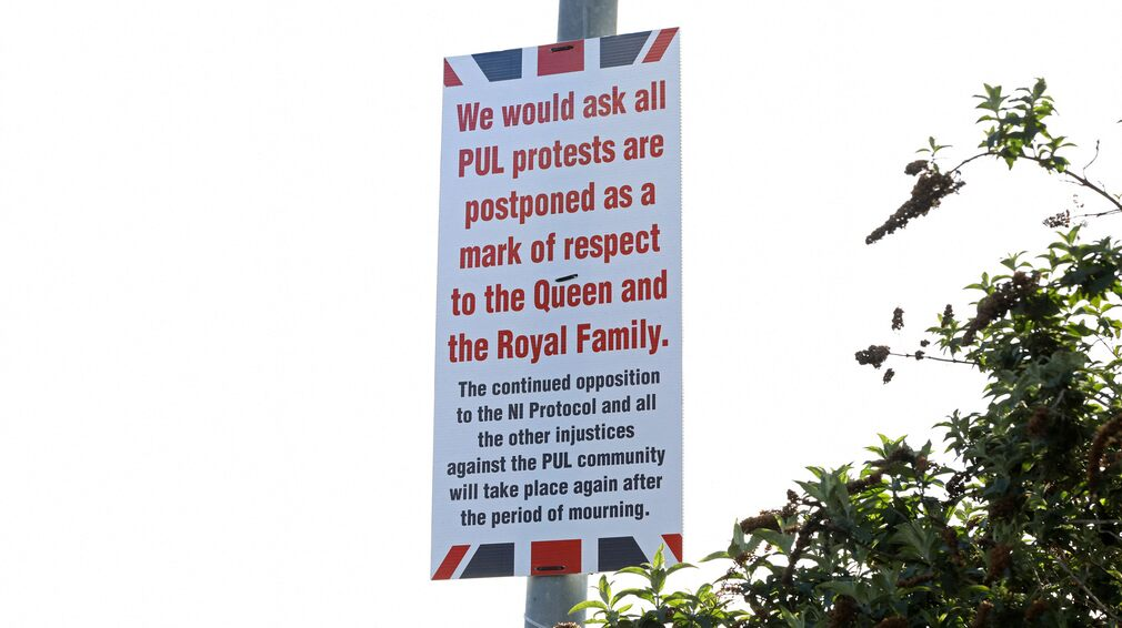 Posters in Belfast call for calm and the suspension of protests over Prince Phillips' death on Friday.