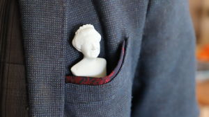 An image of the Queen of Great Britain.  The figure is placed in the chest pocket of the jacket.