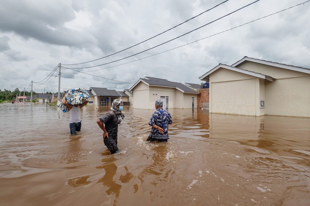 Some residents of Peknabaro, Indonesia, are trying to salvage their property after their homes were flooded after heavy rains on March 29, 2021.