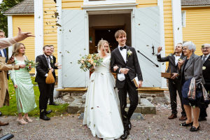 The bride and groom emerge from a yellow wooden chapel.  Upscale wedding guests cast rose petals at the happy bride and groom.