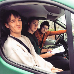 Three boys sitting in a green car looking at the camera.  At the front is Kevin Holmstrom, then Jacob and at the far end is Axel Ohman.
