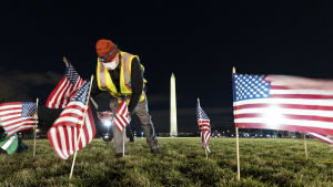 A man puts small American flags on the lawn.