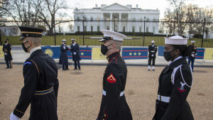 Three people in US Army Military Uniforms walk in front of the camera.  In the background is the White House.  There are two white men and a black woman in the photo.