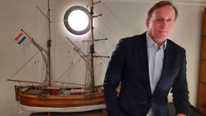 A man in a suit stands next to a model ship