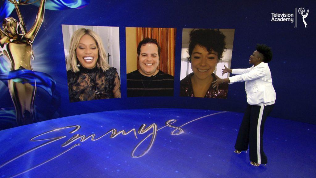 Färgbild från Emmy nomineringarna. En programledare och tre personer på skärmar.