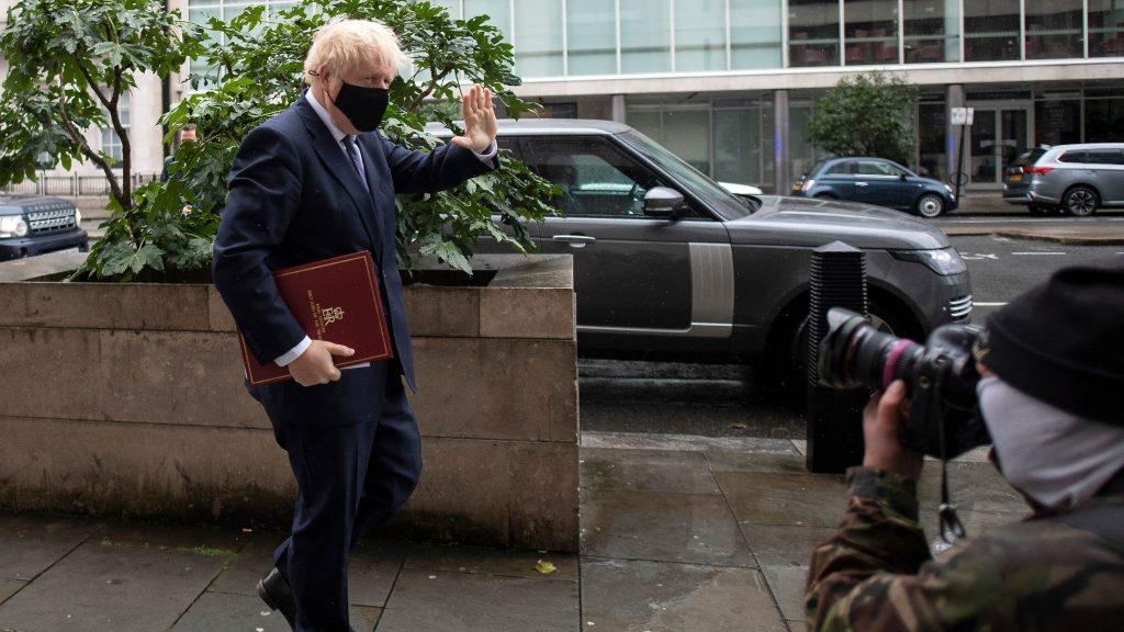 Storbritanniens premiärminister Boris Johnson vinkar mot kamerorna, han bär ansiktsmask.