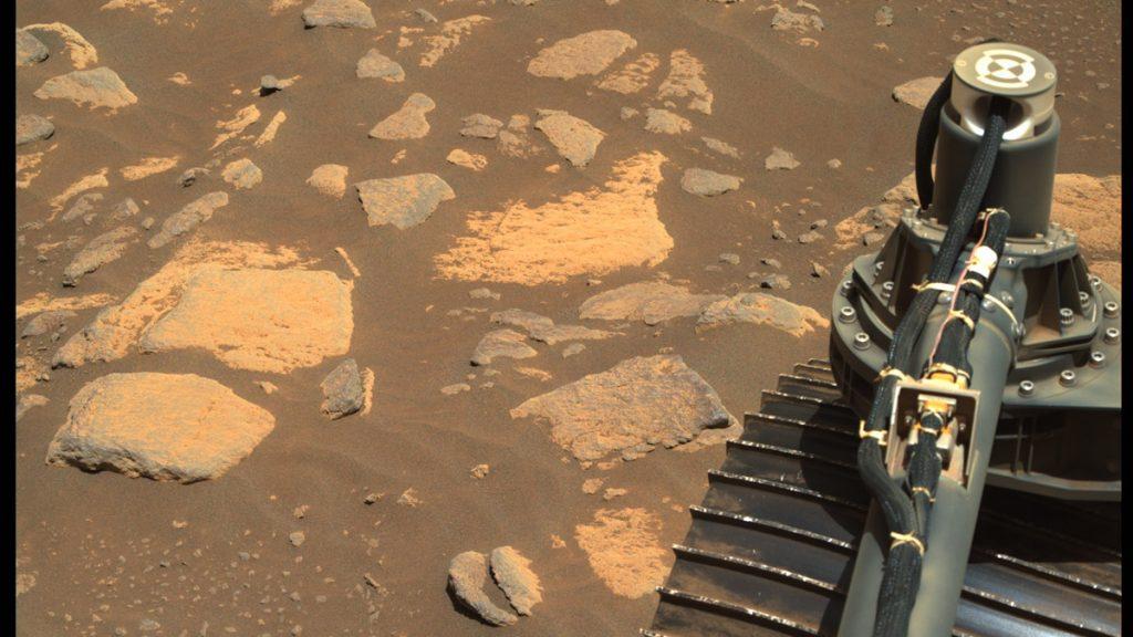 Del av rymdrobot i förgrund, i bakgrunden syns stenar som varit del av en sjöbotten