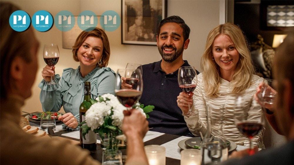 """Stillbild från filmen """"Suedi"""": Personer som skålar i rödvin runt ett middagsbord."""