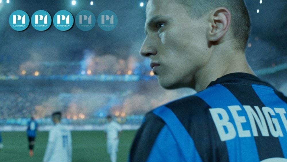 En ung kille i fotbollströja på en fotbollsplan. Han ser sammanbiten ut. På läktarna i bakgrunden brinner bengaliska eldar.